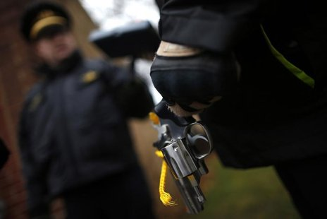 An Evanston police officer holds a firearm that was turned in as part of an amnesty-based gun buyback program in Evanston, Illinois December
