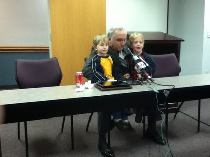 Sheriff Randy Hoenisch during press conference announcing retirement with 4-year-old twin sons Luke and Nathan, emphasizing his family must come first.