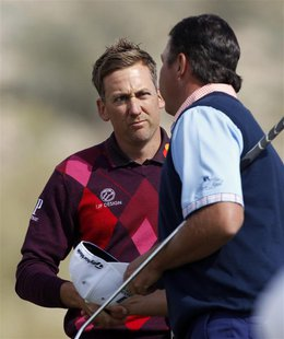Ian Poulter (L) of England shakes hands with Bo Van Pelt of the U.S. on the 17th hole after their second round match of the WGC-Accenture Ma