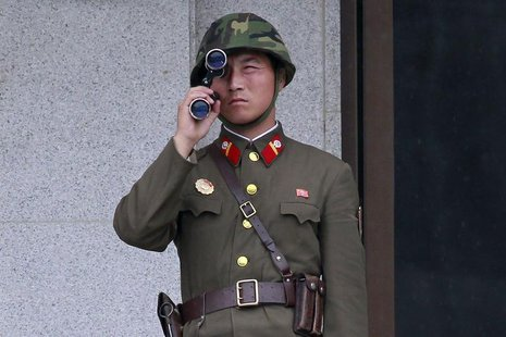 A North Korean soldier looks south through a pair of binoculars on the north side of the truce village of Panmunjom in the demilitarised zon