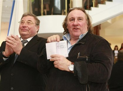 French film star Gerard Depardieu (R) shows his passport with residency permit as Vladimir Volkov, head of the Republic of Mordovia, applaud