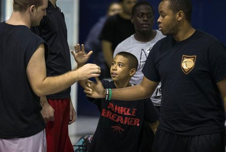 Downey Christian high school varsity basketball player 11-year-old Julian Newman (C) greets other participants during Friday evening pickup