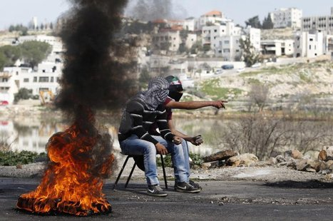 Palestinians hold stones as they sit next to a burning tyre during clashes with Israeli troops outside Israel's Ofer military prison near th