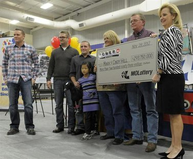 The Hill family holds an oversized check presented by Missouri Lottery director May Scheve (R) during a news conference at the North Platte
