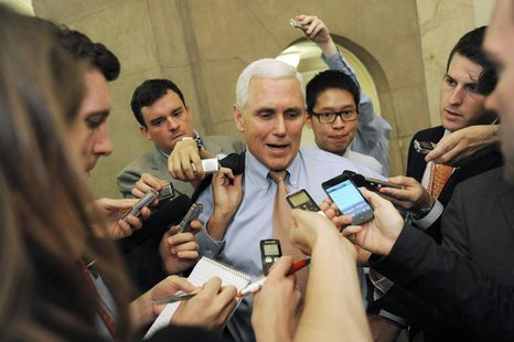 U.S. Representative Mike Pence (R-IN) (C) talks with reporters as he departs a meeting about debt ceiling legislation with fellow Republican