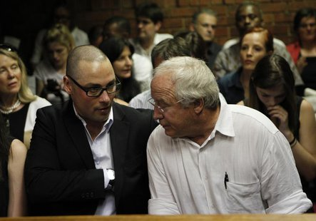 Oscar Pistorius' brother Carl and father Henke await the start of court proceedings in the Pretoria Magistrates court February 20, 2013. REU
