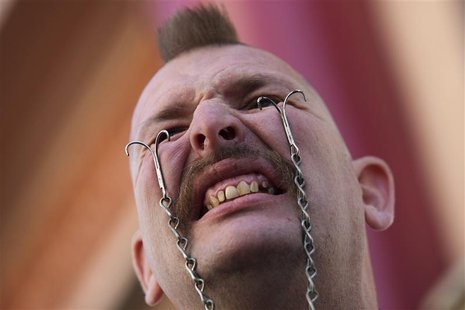 Performance artist George the Giant attaches hooks into his eyelids to hold a soda bottle ahead of the sixth annual World Sword Swallower's