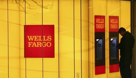 A man uses an automated teller machine (ATM) at a Wells Fargo Bank branch on a rainy morning in Washington January 17, 2012. REUTERS/Gary Ca