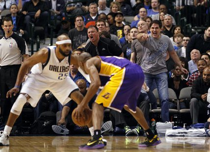 Dallas Mavericks owner Mark Cuban (R) reacts as guard Vince Carter (L) guards Los Angeles Lakers guard Kobe Bryant during the second half of