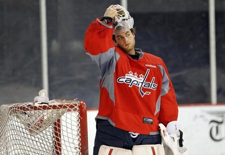 Washington Capitals goalie Braden Holtby puts on his mask as he works out at the team's facility in Arlington, Virginia January 8, 2013.REUT
