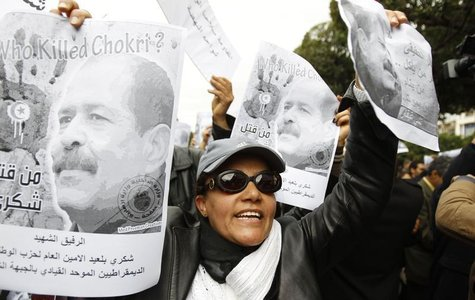 A woman chants slogans and holds pictures of assassinated leftist politician Chokri Belaid during a demonstration against the Islamist Ennah
