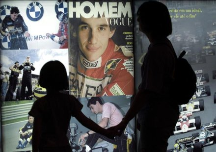 "Visitors look at pictures of Brazilian Formula One driver Ayrton Senna displayed at the ""Ayrton Senna Trajectory"" exhibition in Sao Paulo, M"