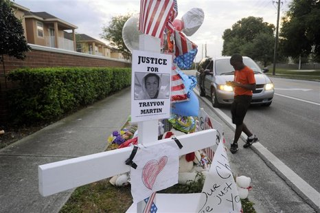 Jaquez Forest, 12, of Sanford, Florida, photographs a memorial for Trayvon Martin in Sanford, Florida, in this March 29, 2012 file photo. A