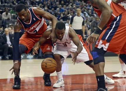 Toronto Raptors Kyle Lowry (3) is fouled by Washington Wizards John Wall (2) during the first half of their NBA basketball game in Toronto,