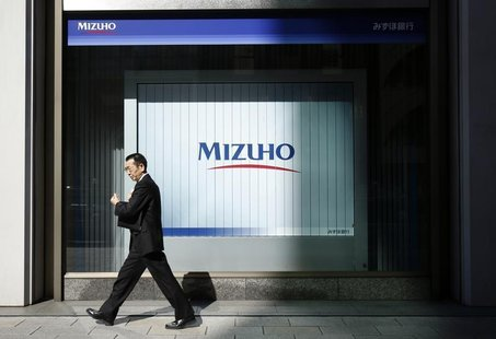 A man walks past a branch of Mizuho bank belonging to Mizuho Financial Group in Tokyo February 25, 2013. REUTERS/Yuya Shino