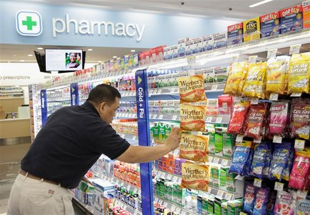 "A worker stocks a new Walgreens store in Chicago January 9, 2012. Walgreen Co is going through ""the worst"" part of not being in Express Scri"