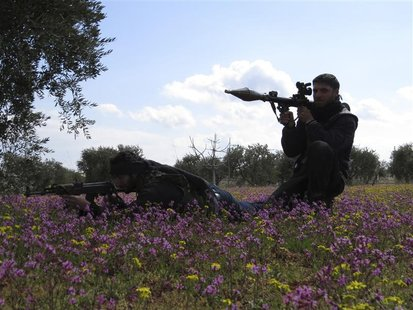 Free Syrian Army fighters hold their weapons and take positions in preparation for what they say is an ambush against forces loyal to Syria'