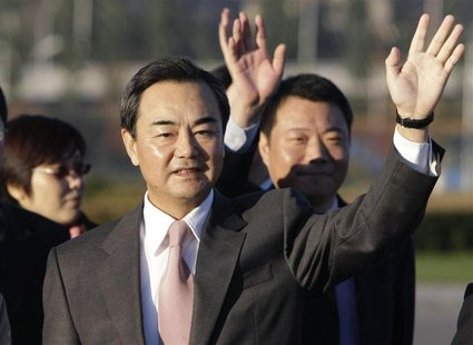 Wang Yi, the director of China's National Taiwan Affairs Office, waves to see Chen Yunlin (not in picture), chairman of China's Association
