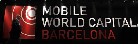 A visitor walks past a Mobile World banner at the Mobile World Congress in Barcelona, February 26, 2013. The GSMA Mobile World Congress, rep