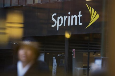 People walk past a Sprint store in New York December 17, 2012. Clearwire Corp agreed to sell roughly half of the company for $2.2 billion to