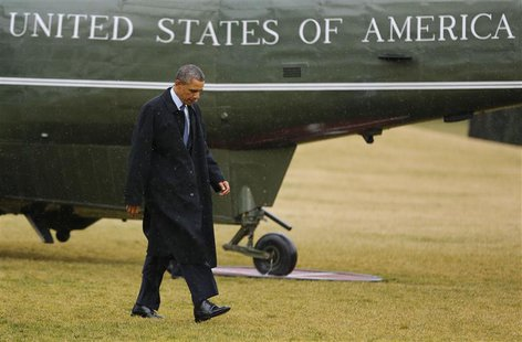U.S. President Barack Obama walks on the South Lawn after stepping off Marine One in the rain after returning to the White House in Washingt