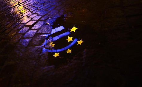 The Euro sculpture is partially reflected in a puddle on a cobblestone pavement in front of the headquarters of the European Central Bank (E