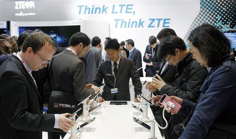 Visitors look at devices at ZTE booth at the Mobile World Congress in Barcelona, February 26, 2013. REUTERS/Albert Gea