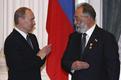 Russia's President Vladimir Putin (L) applauds after he decorated Russian State Duma member Artur Chilingarov, the leader of the 2007 Arctic