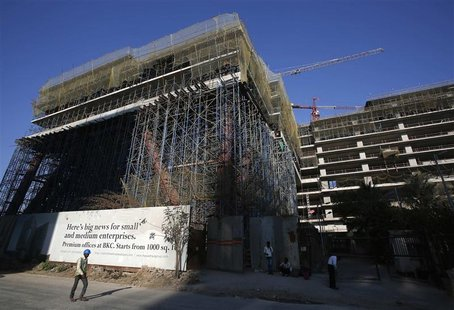 A worker walks in front of the under-construction One BKC commercial complex, being built by The Wadhwa Group, in the Bandra-Kurla Complex i