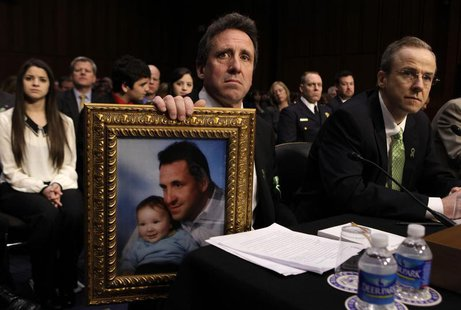 Neil Heslin, holds a picture of himself and his 6-year-old son, Newtown victim Jesse Lewis, during the Senate Judiciary Committee hearing on