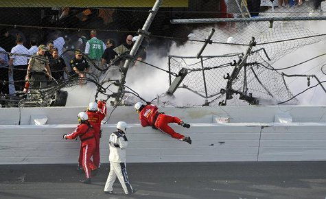 Rescue workers respond next to a hole in the catch fence following a last-lap incident during the NASCAR Nationwide Series DRIVE4COPD 300 ra
