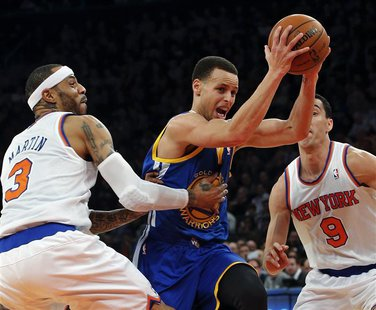 Golden State Warriors guard Stephen Curry (C) drives between New York Knicks forward Kenyon Martin (3) and guard Pablo Prigioni (9) in the s