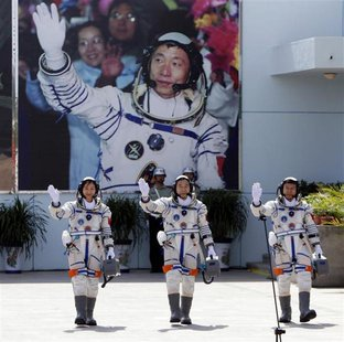 Chinese astronauts Jing Haipeng (C), Liu Wang (R) and Liu Yang, China's first female astronaut, wave in front of a picture of the first astr
