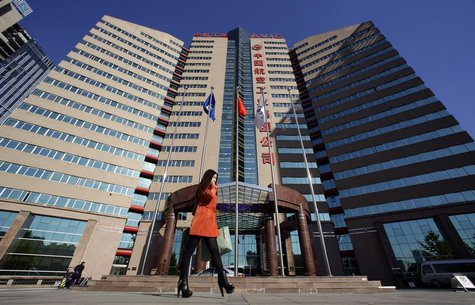 A woman walks past the Aviation Industry Corporation of China (AVIC) headquarters building in Beijing October 30, 2012. REUTERS/Jason Lee
