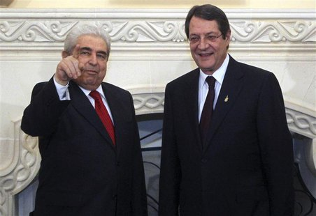 Cyprus's new President Nicos Anastasiades (R) stands next to his predecessor Demetris Christofias at the presidential palace in the capital
