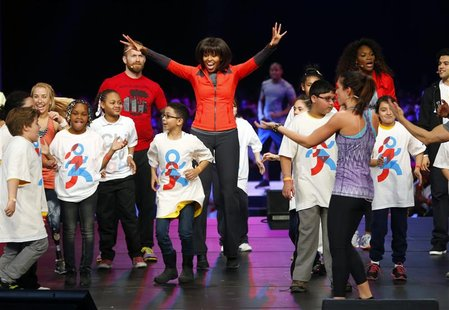 U.S. first lady Michelle Obama dances on stage with school children during an event to bring physical activity back to schools, hosted by th
