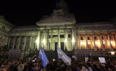 People wave Argentine flags as they attend a demonstration to protest against an agreement between Argentina and Iran outside the Argentine