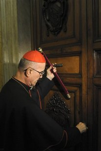 Cardinal Tarcisio Bertone seals the door of the apartment of Pope Benedict XVI at the Vatican February 28, 2013. REUTERS/Osservatore Romano