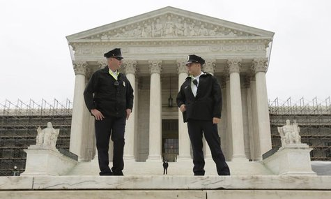 Two policemen talk in front of the U.S. Supreme Court in Washington June 18, 2012. REUTERS/Kevin Lamarque