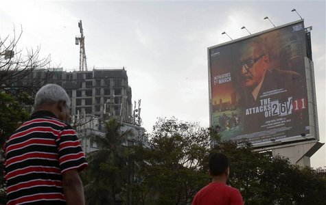 "People walk underneath a promotional billboard for Ram Gopal Varma's film ""The Attacks of 26/11"" by a roadside in Mumbai February 28, 2013."