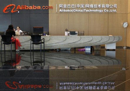 An employee serves a guest at the reception counter inside the headquarters office of Alibaba (China) Technology Co. Ltd on the outskirts of