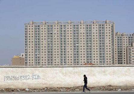 A man walks past a wall at a construction site at a new residential area in Beijing February 27, 2013. REUTERS/Kim Kyung-Hoon