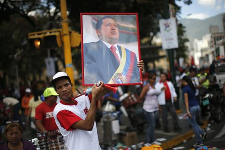 A supporter of Venezuela's President Hugo Chavez holds up a portrait of him while attending a rally in Caracas February 27, 2013. REUTERS/Jo