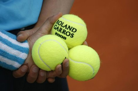 A ball boy holds tennis balls during an exhibition match ahead of the French Open tennis tournament at the Roland Garros stadium in Paris in