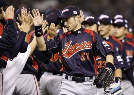 Japan's Ichiro Suzuki (C) celebrates with team mates after defeating South Korea during the World Baseball Classic (WBC) Tokyo round in Toky