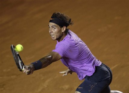 Rafael Nadal of Spain hits a return to compatriot Nicolas Almagro during their men's singles match at the Acapulco International tennis tour