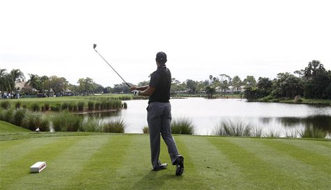 Tiger Woods of the U.S. follows through on a tee shot on the 13th hole during the third round play at the Honda Classic PGA golf tournament
