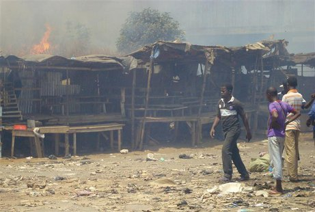 Men stand and watch as a fire rages in the background during clashes between rival gangs in Marche Madina, in Conakry March 1, 2013. REUTERS