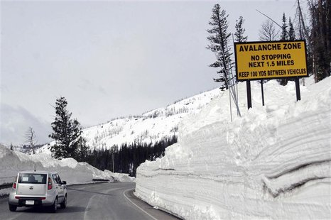A car travels the newly plowed east entrance road over Sylvan Pass in Yellowstone National Park shortly after the park opened in this photo