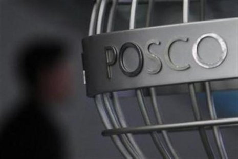 A man walks past a POSCO logo at the company's headquarters in Seoul April 22, 2011. REUTERS/Truth Leem/Files